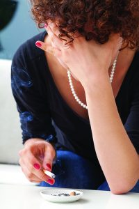 A depressed woman smoking cigarettes one by one